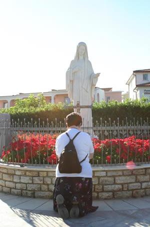Gabriela de frente para Estátua de Nossa Senhora Rainha da Paz